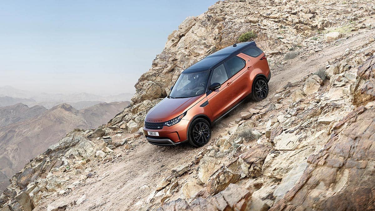 2018 Land Rover Discovery driving down rocky gravel hill