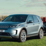 Land Rover Discovery Sport driving through grassing field towing a flatbed carrying building materials