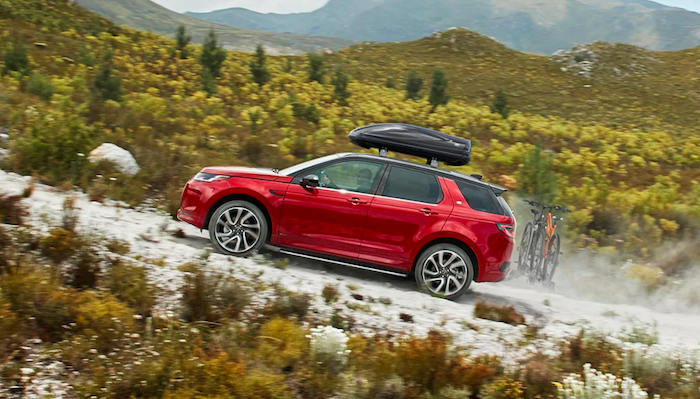 Red Discovery Sport with bicycles on back driving up gravel road near the mountains