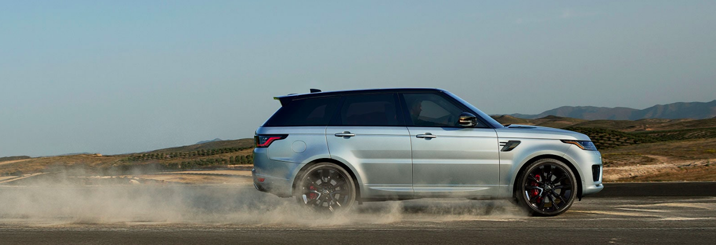 Range Rover Sport driving and kicking up gravel on road