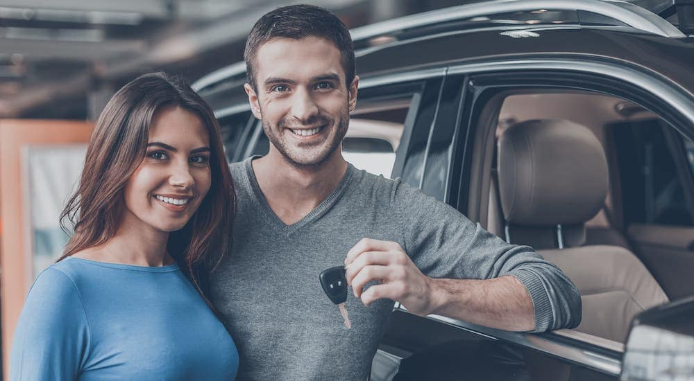 A happy couple are holding car keys and leaning on a black SUV.