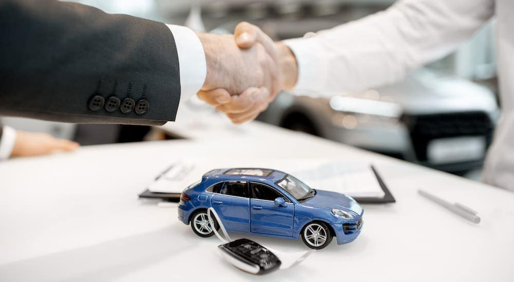 Two hands are shaking over a blue toy car, car keys, and paperwork at a buy here pay here dealership.