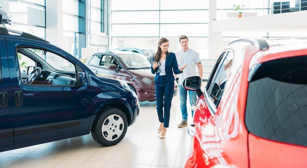 A saleswoman is showing a man through a car showroom.