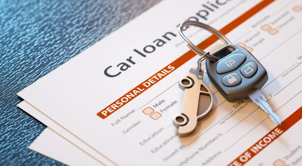 An application for a car loan is on a table with a key.
