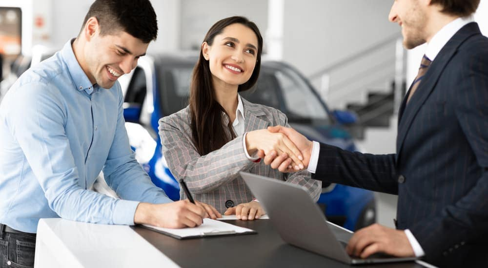 A couple is filling out paperwork at a Buy Here Pay Here dealership.