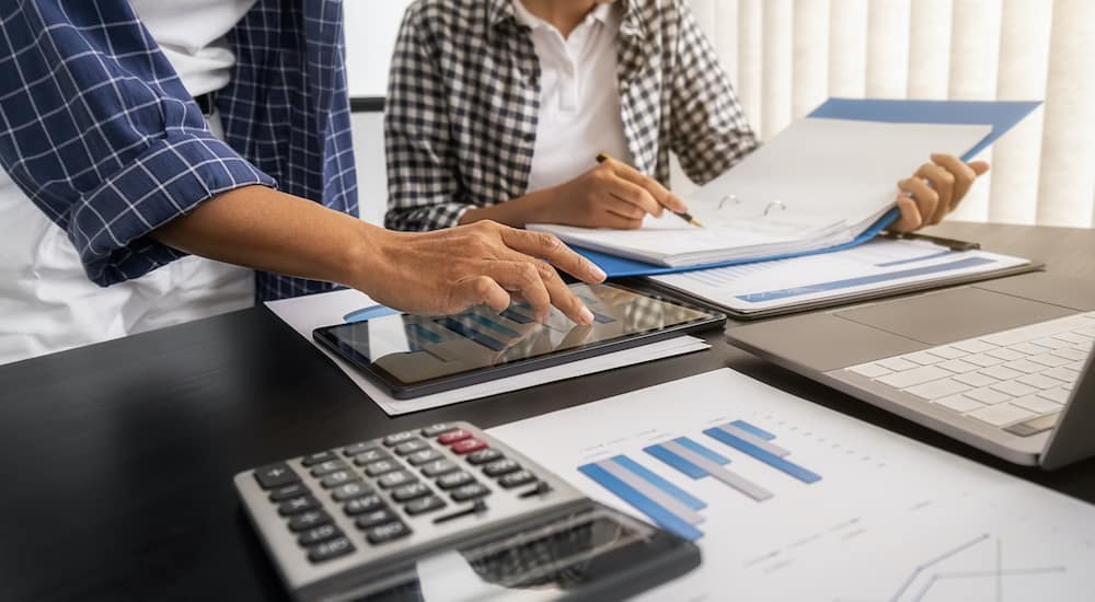 A man and woman are financing with a calculator and tablet.