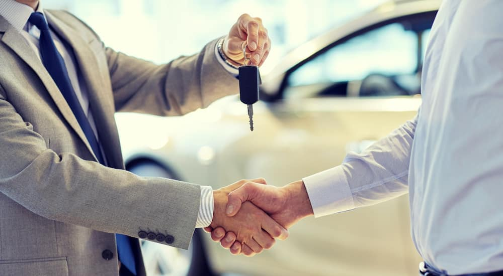 A car salesman is shaking someone's hand as he holds out a set of keys at a Buy Here Pay Here in Ohio.