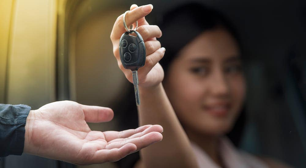 A woman is sitting inside a car and handing keys to a car dealer while selling her car fast.