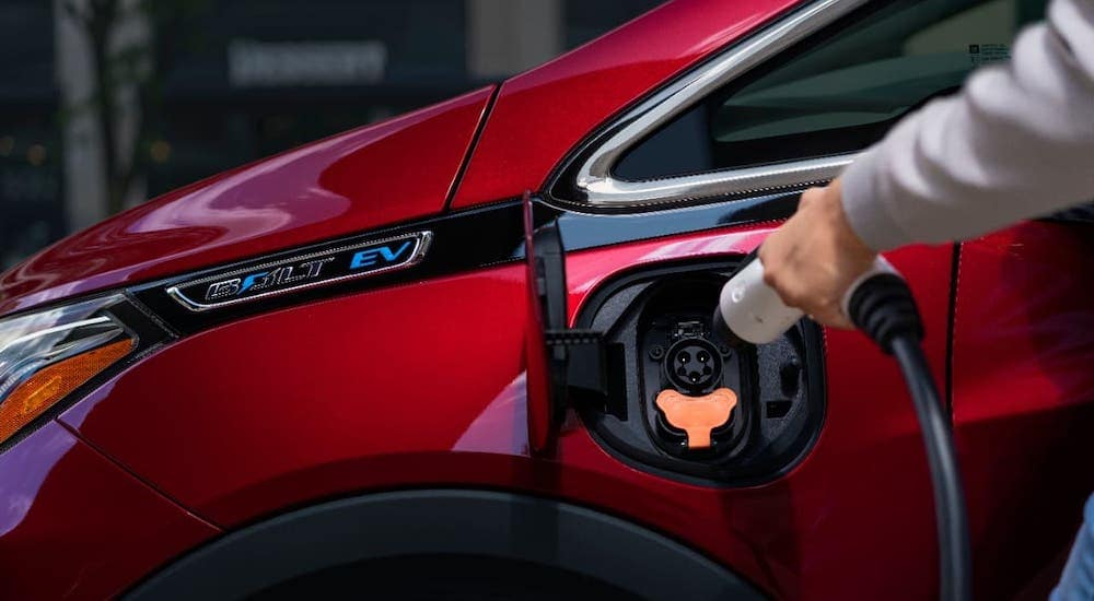 A closeup shows the charging port on a red 2016 Chevy Bolt EV.