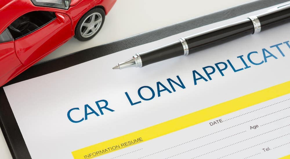 A car loan application is shown with a red toy car.