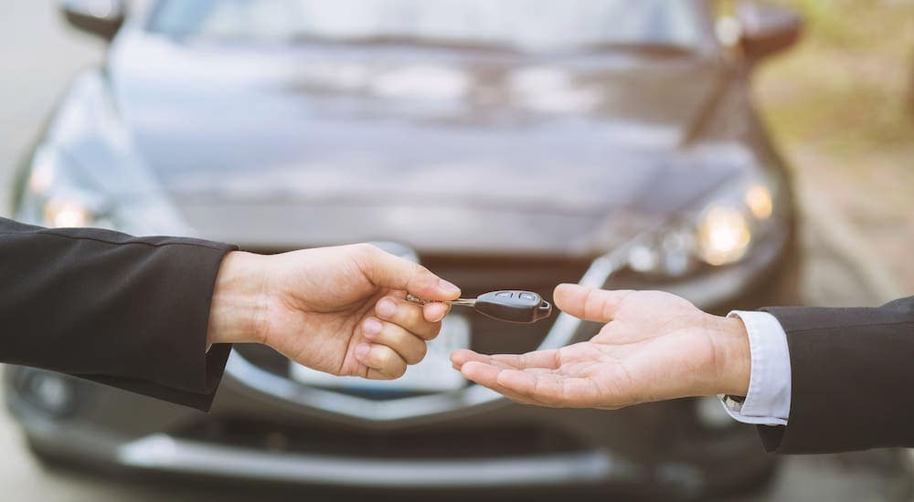 One hand is shown giving a key to another hand in front of a gray car.