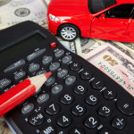 A red toy car, calculator and red colored pencil are sitting on $50 bills signifying auto loan interest rates.