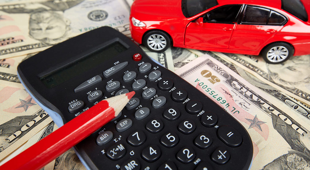 A red toy car, calculator and red colored pencil are sitting on $50 bills.