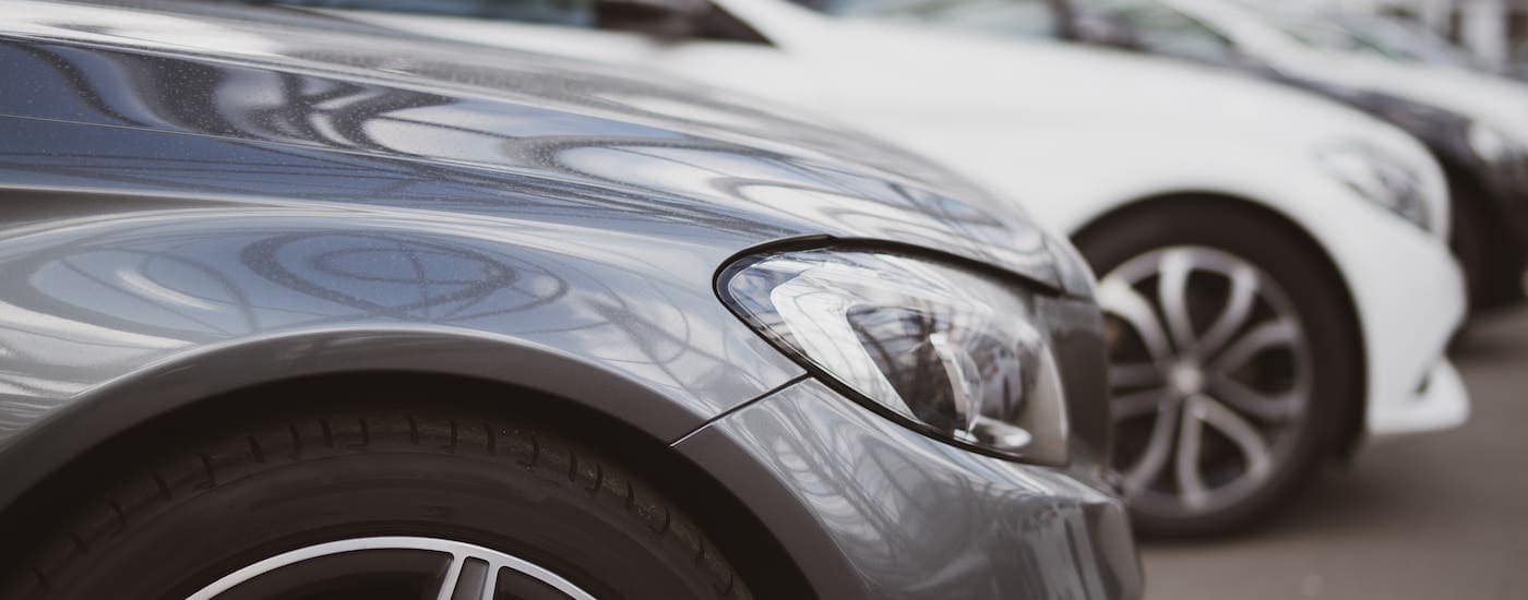 A closeup is shown of a row of used cars on a buy here pay here dealership lot.