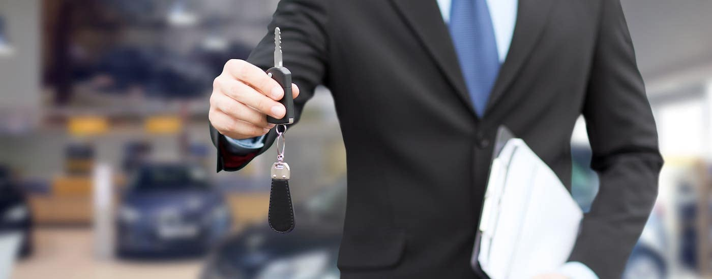 A salesman is holding car keys and a clipboard in a car showroom.
