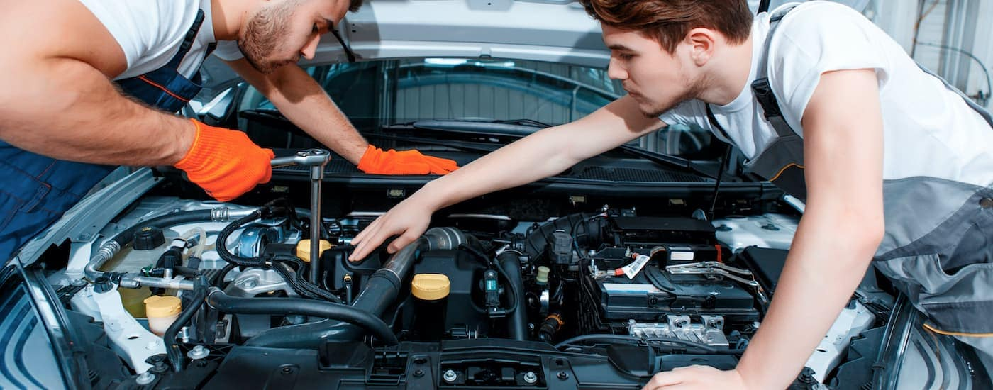 Two mechanics are shown working on a car engine.