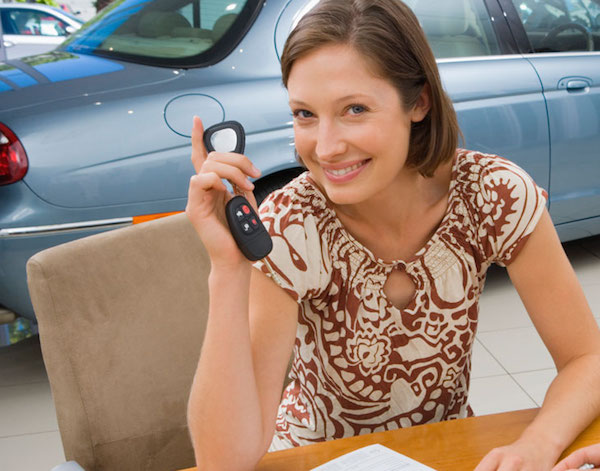 A woman is holding keys at a Buy Here Pay Here dealership in Cincinnati.