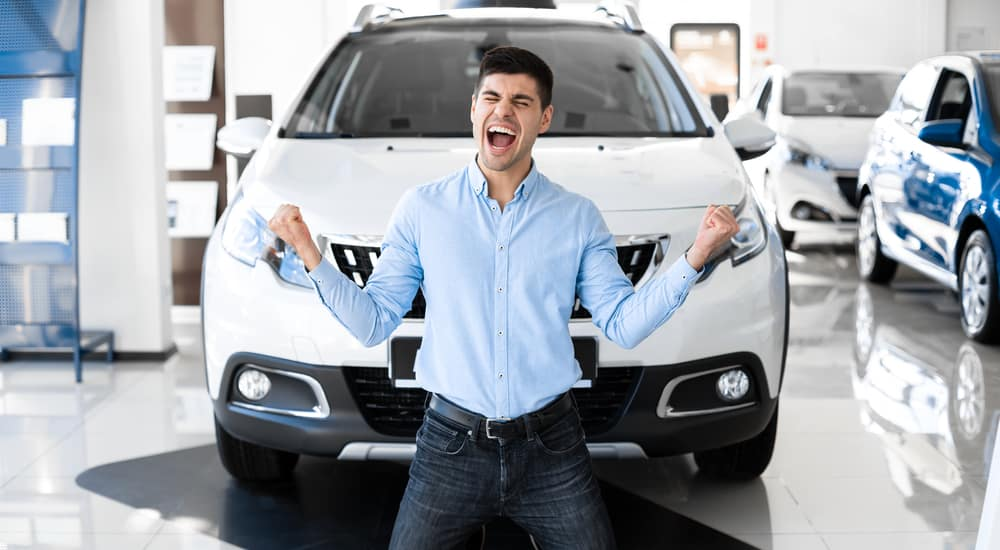 Man kneeling in front of a white SUV smiling with his mouth open and pumping his arms excitedly