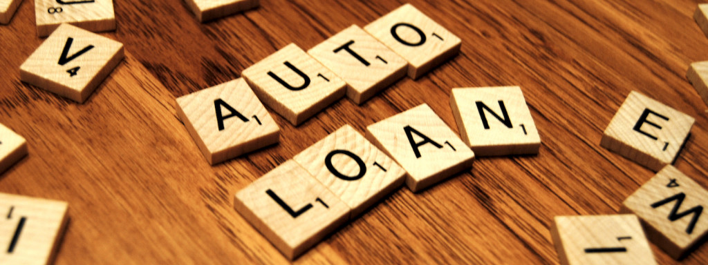 The words Auto Loan are spelled out in Scrabble letters on a table.