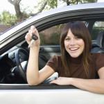 A woman is leaning out of a white car, smiling, and holding keys after getting a bad credit car loan in Cincinnati.