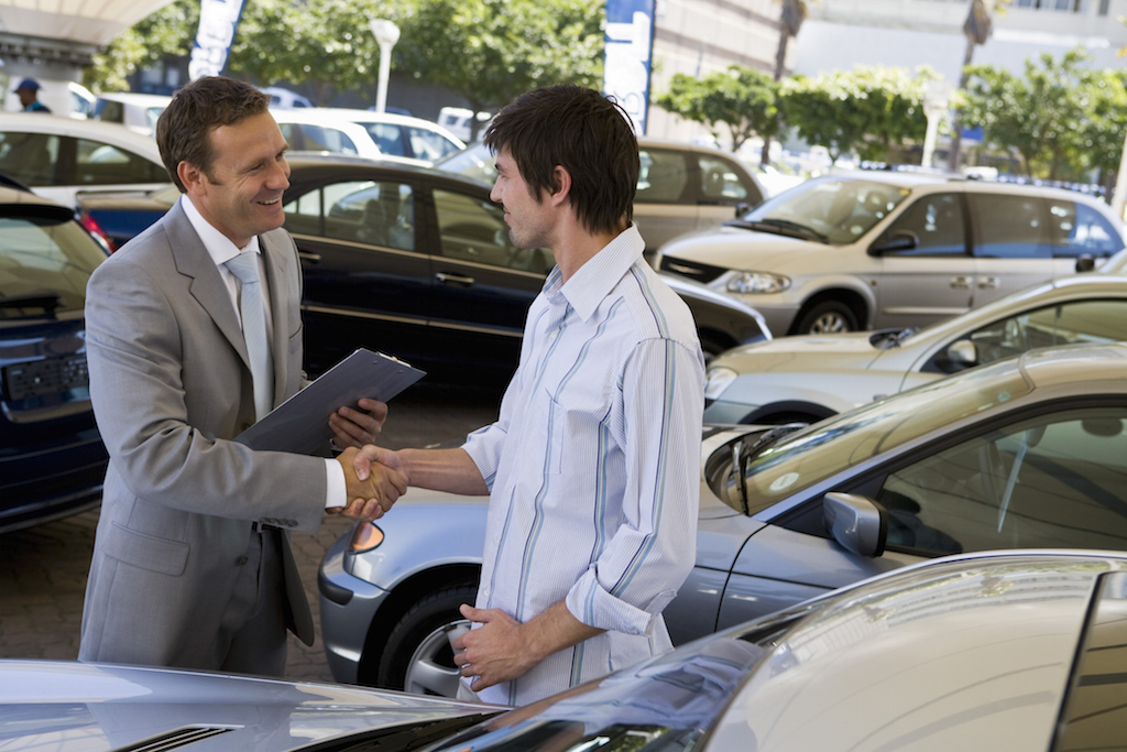 Salesman showing man a car