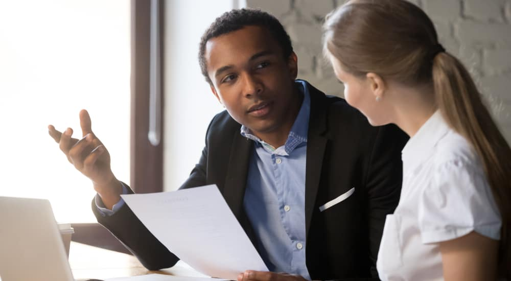 Man in a black jacket and blue shirt explaining something with a paper to a woman in a white shirt