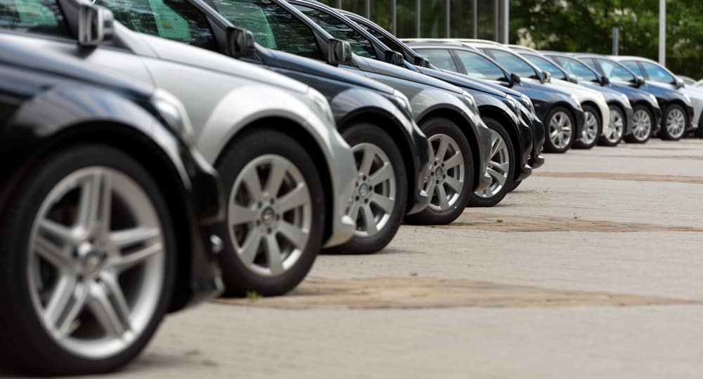 Black and silver cars in a line, parked diagonally