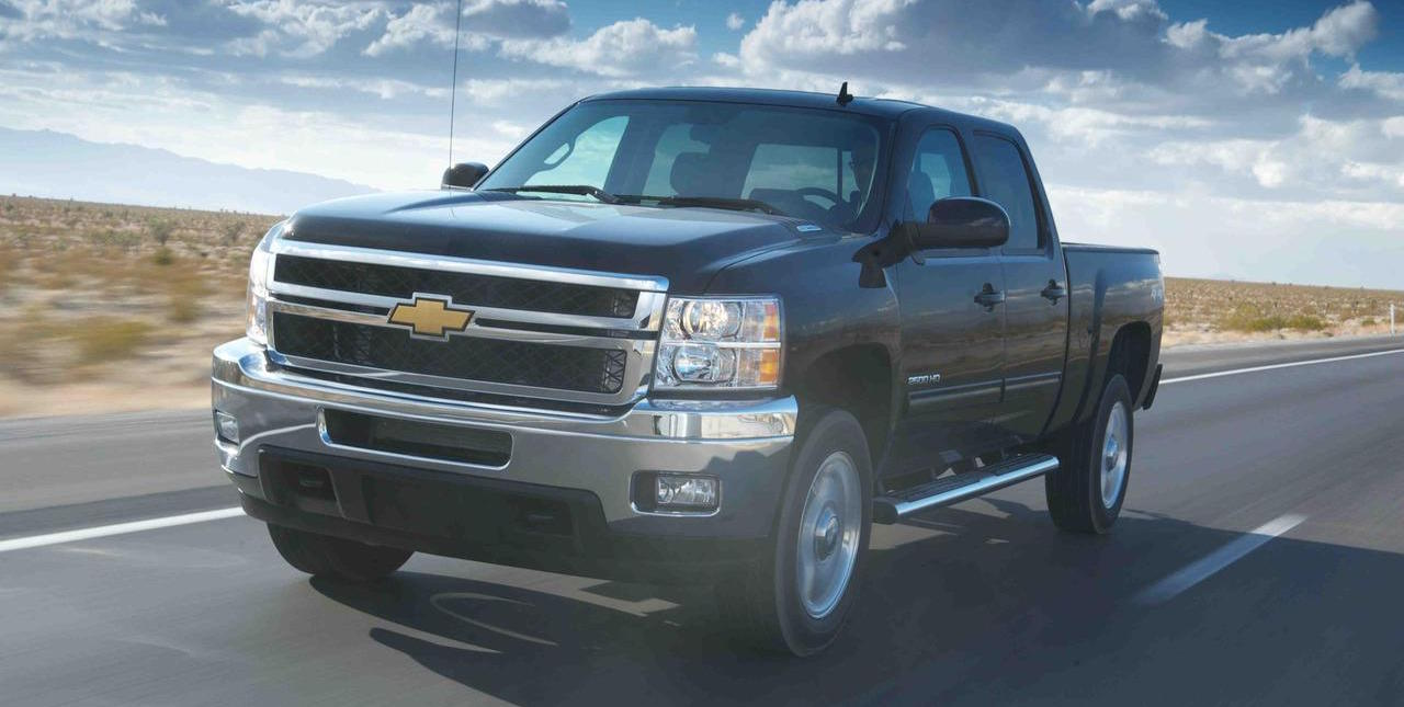 Black 2012 Used Chevy Silverado 2500HD driving on desert road against blue cloudy sky