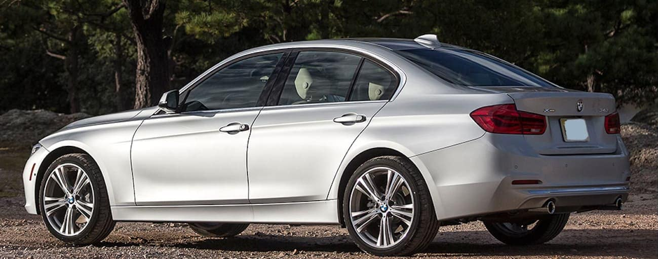 A silver 2017 BMW 3 Series is parked in a dirt parking lot near Cincinnati, OH.
