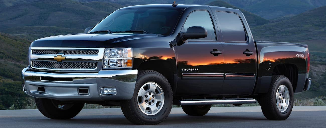 A black 2012 used Chevy Silverado is parked in front of mountains with a sunset reflecting in the reflection