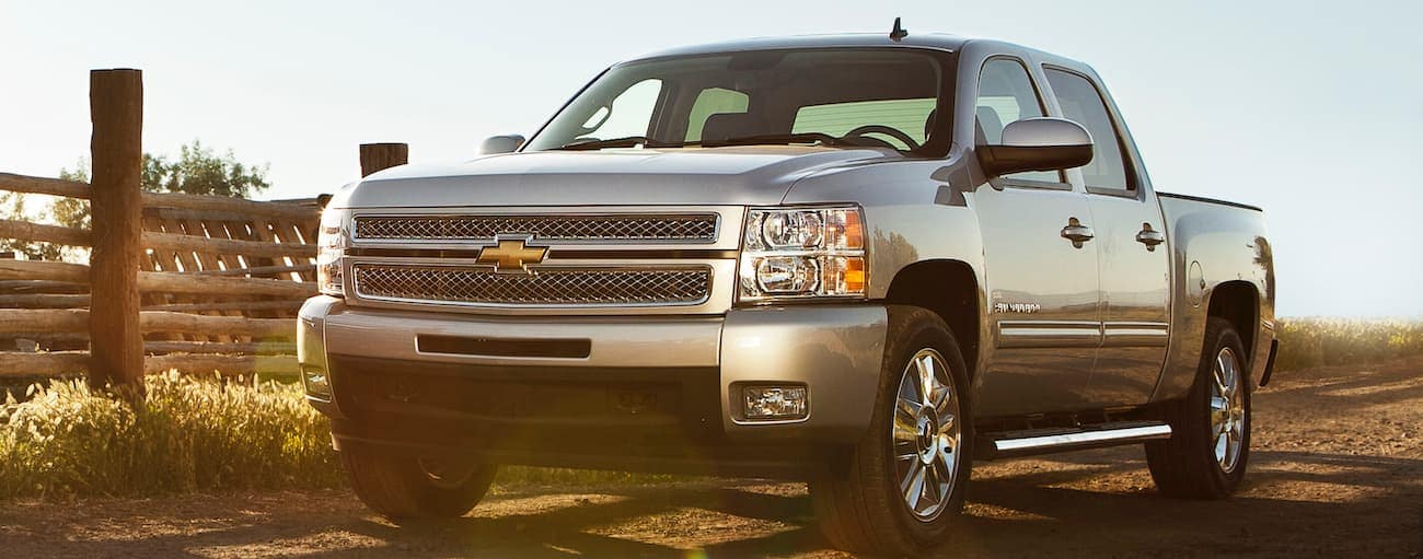 A silver 2013 used Chevy Silverado is driving past a wooden fence