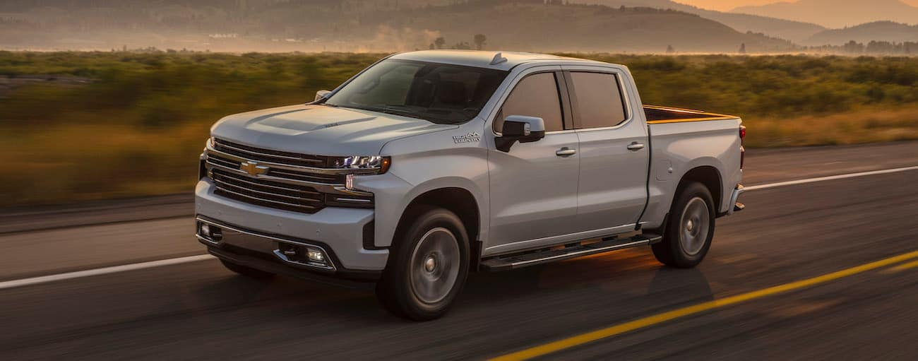 A white 2019 used Chevy Silverado is driving in a desert at sunset.