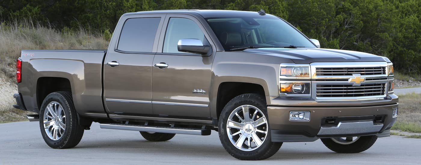 A grey 2014 used Chevy Silverado High Country is parked in front of trees.