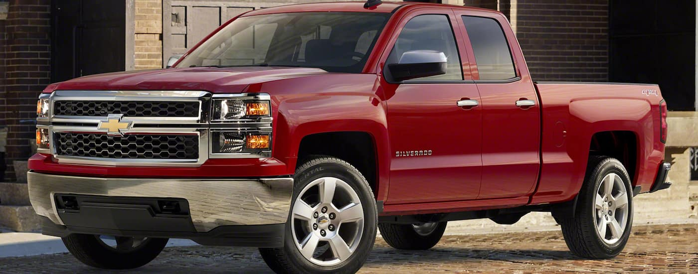 A red 2015 used Chevy Silverado 1500 Custom is parked in front of a brick building.