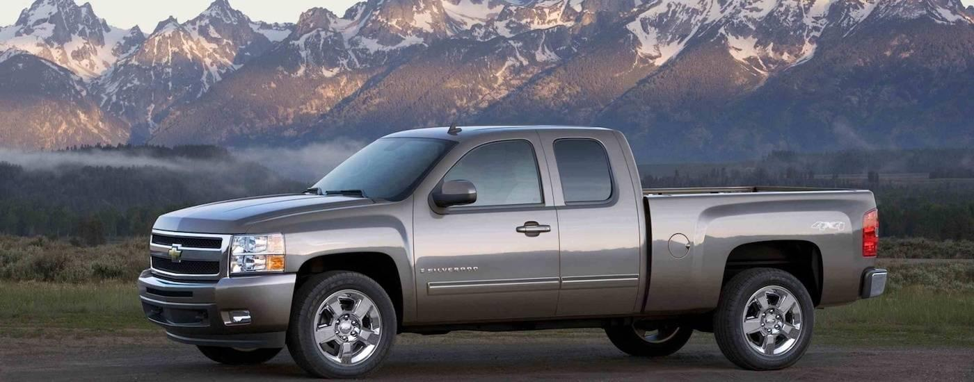 A silver 2009 Used Chevy Silverado LTZ Extended Cab is in front of mountains.