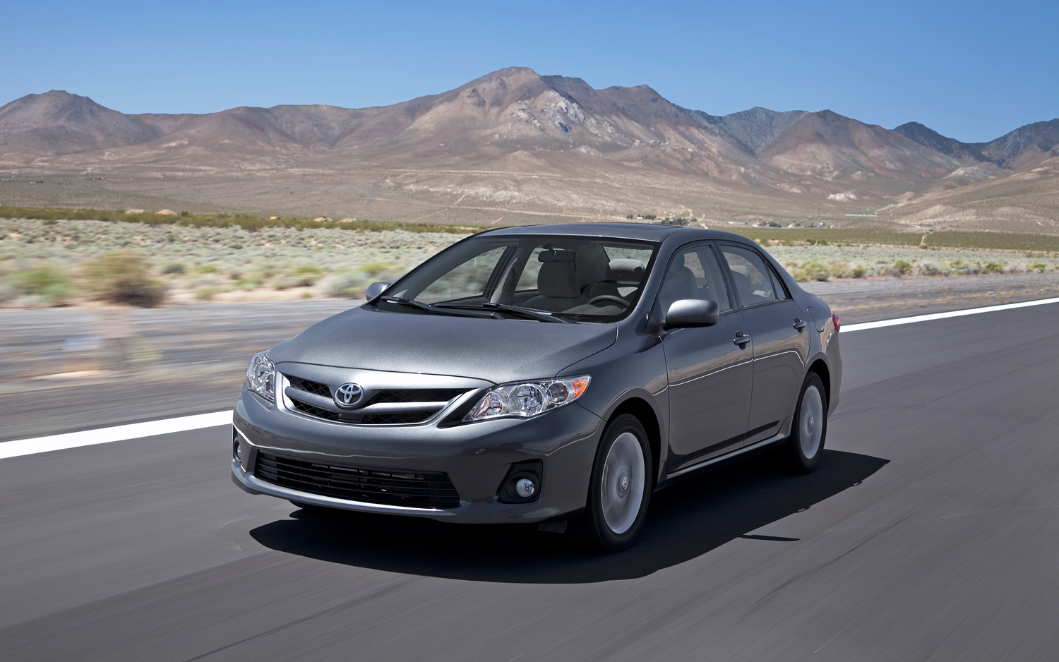 Silver 2011 Used Toyota Corolla in desert with mountains in back