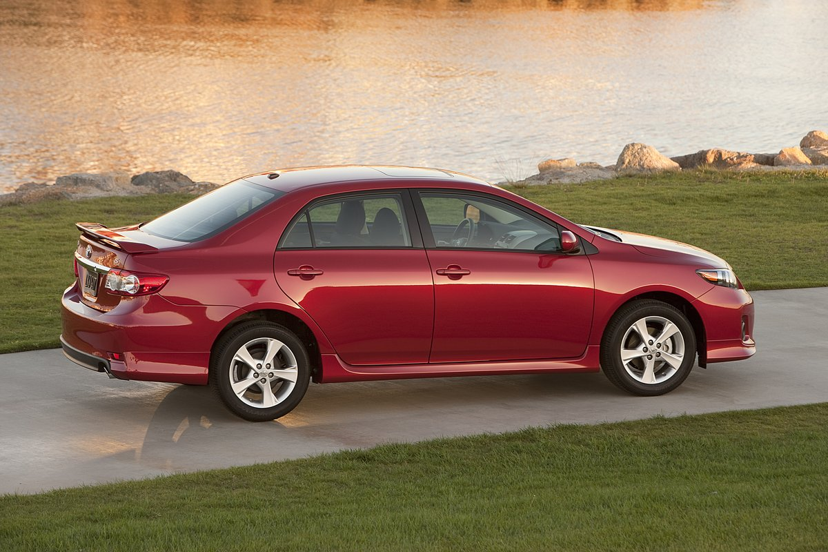 Profile of a Red 2013 Used Toyota Corolla in front of a pond