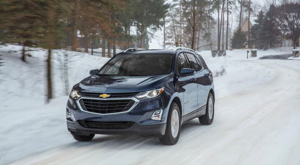 A dark blue 2018 Chevy Equinox is driving on a snowy road.