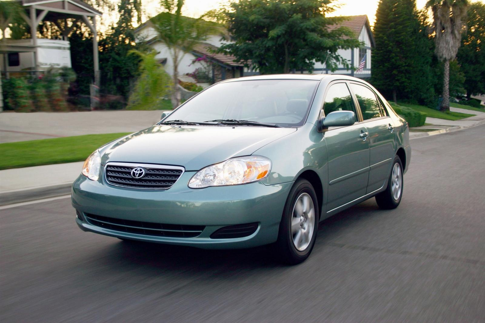 Light Blue 2009 Used Toyota Corolla driving on a suburban street