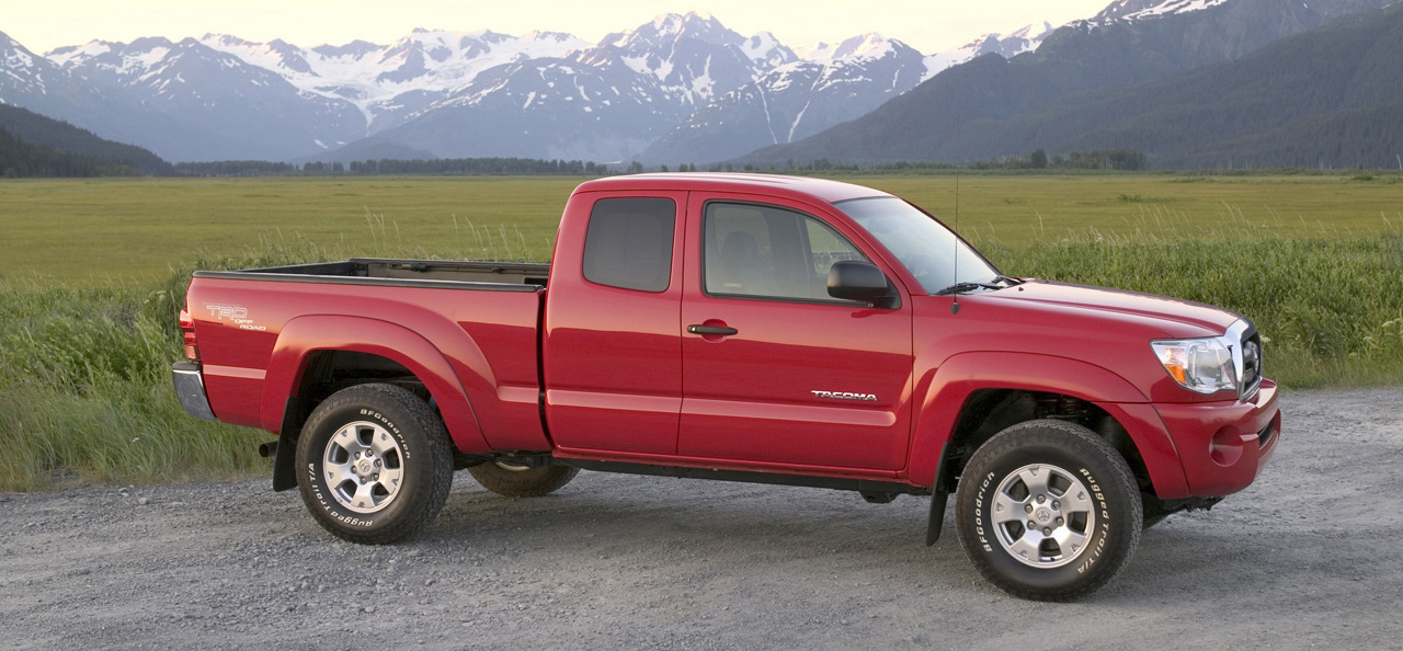 Red 2008 Used Toyota Tacoma parked in front of mountains and fields