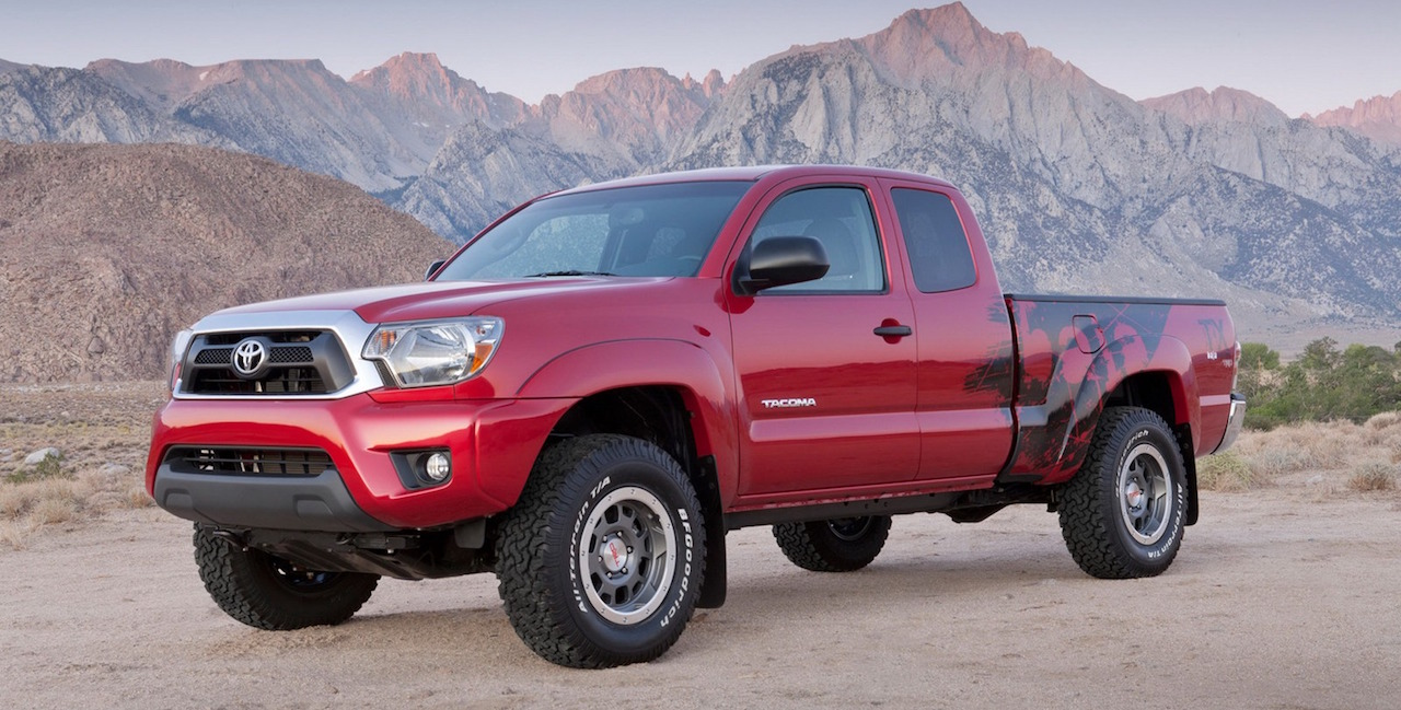 Red 2012 Used Toyota Tacoma with custom paint job parked in front of the mountains