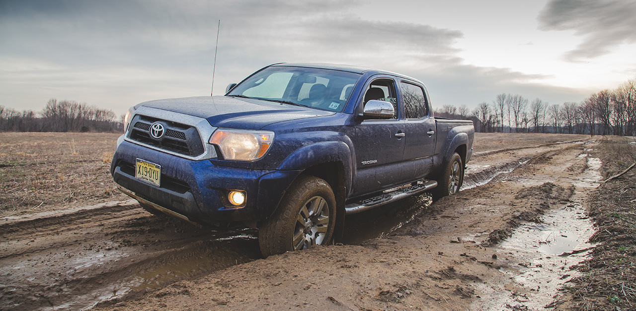 Blue 2014 Used Toyota Tacoma driving through mud against cloudy gray sky