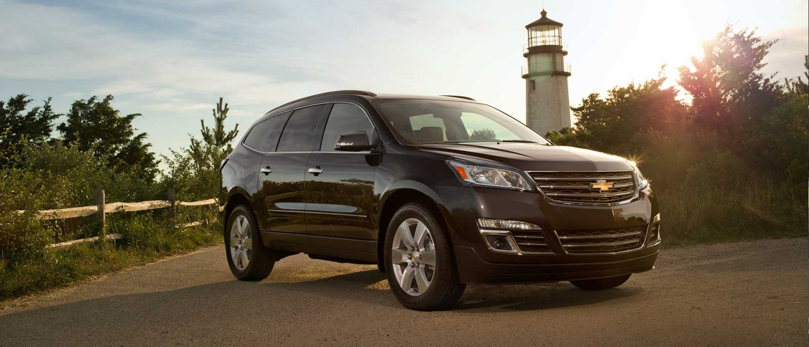 A black 2014 used Chevy Traverse is parked in front of a lighthouse.