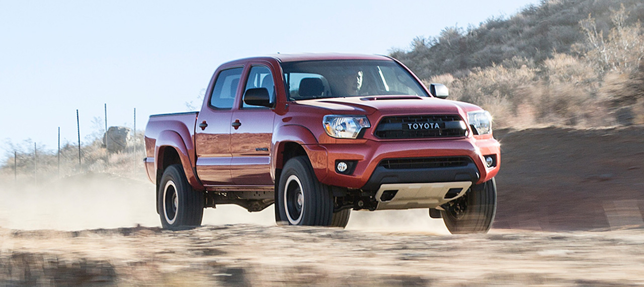 Red 2015 Used Toyota Tacoma driving fast through desert