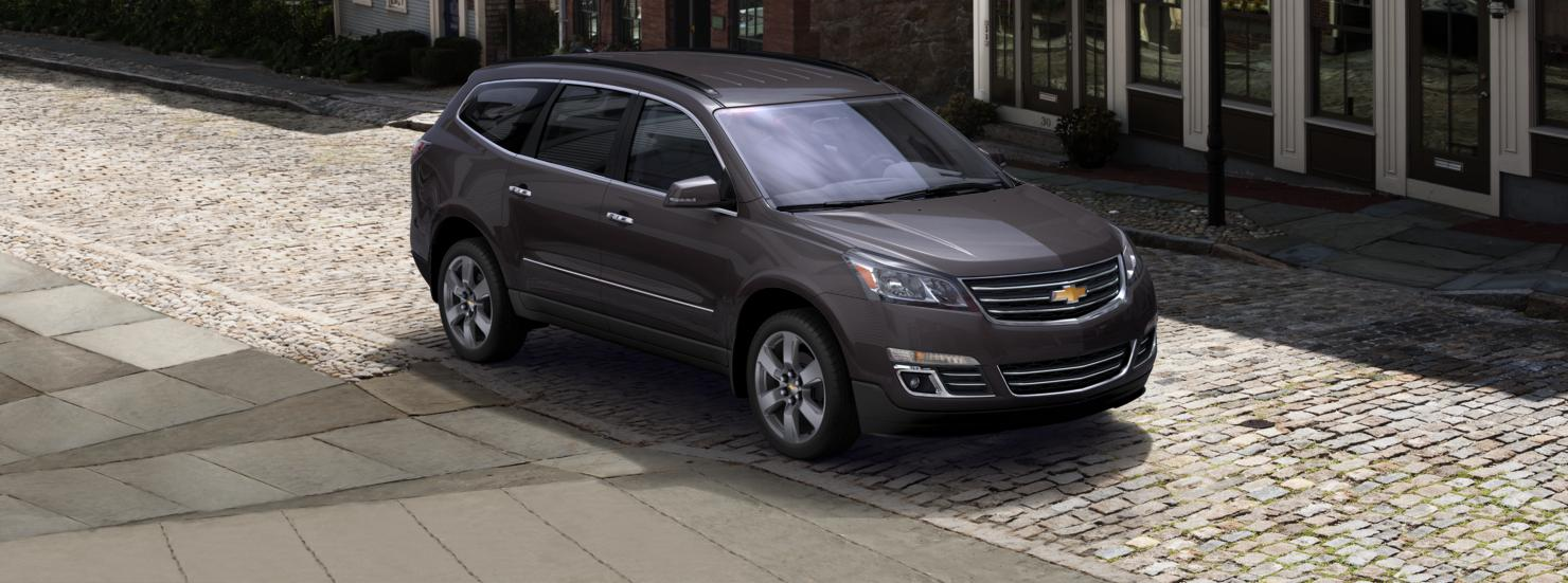 A dark grey 2015 used Chevy Traverse is parked on a cobble street.
