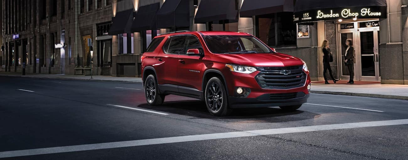 A red 2019 used Chevy Traverse is parked at an intersection at night.