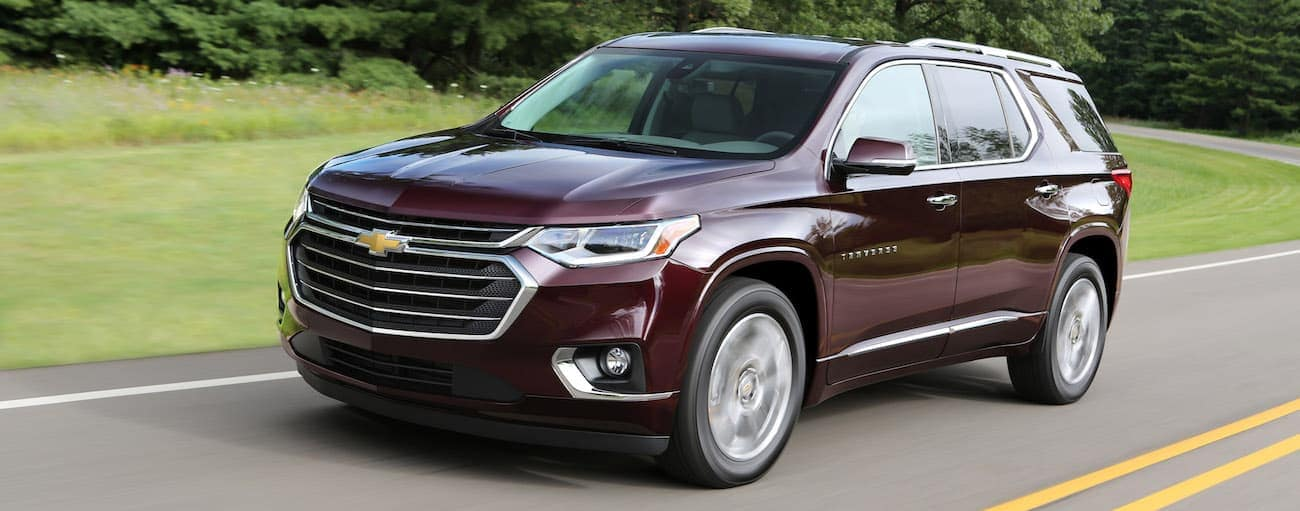 A burgundy 2018 used Chevy Traverse is driving along a road outside of Cincinnati, OH.