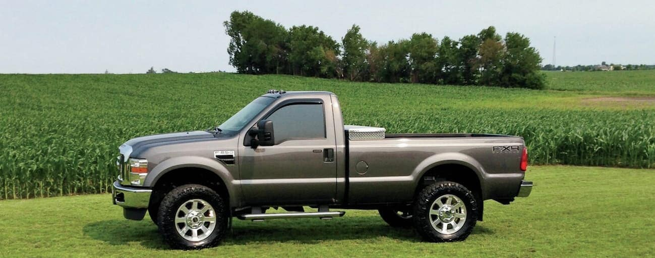 A gold 2008 Ford F-250 is parked on grass next to a corn field.