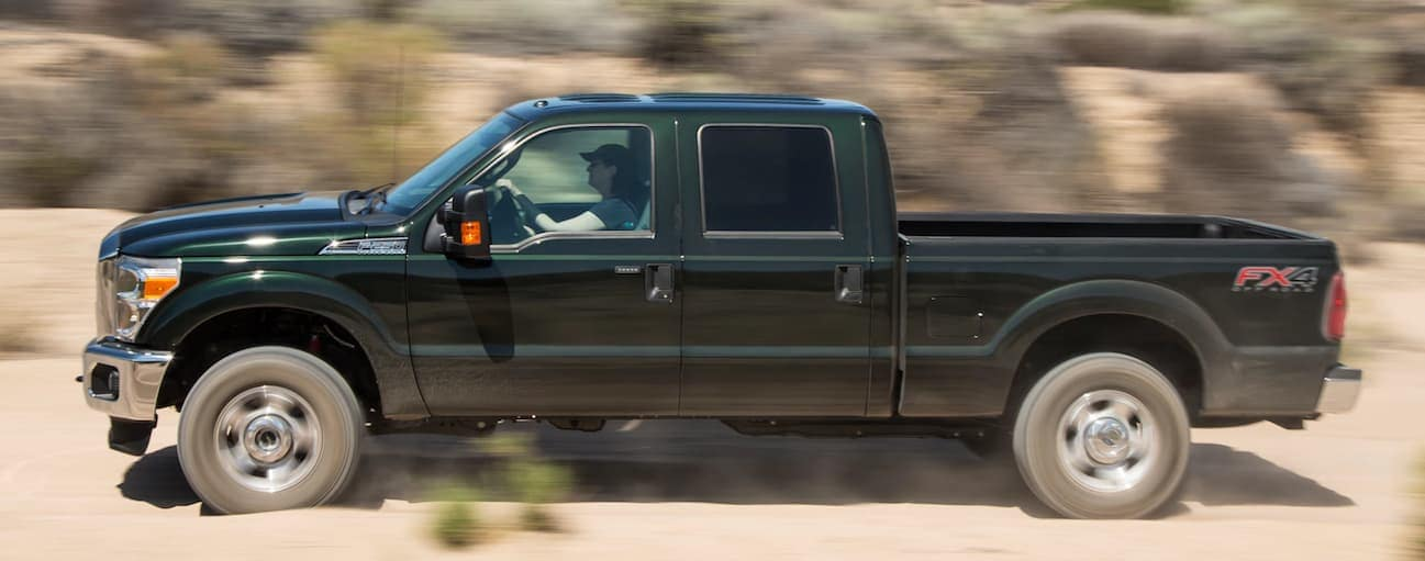 A side view of a green 2013 F-250 driving on a dirt road.