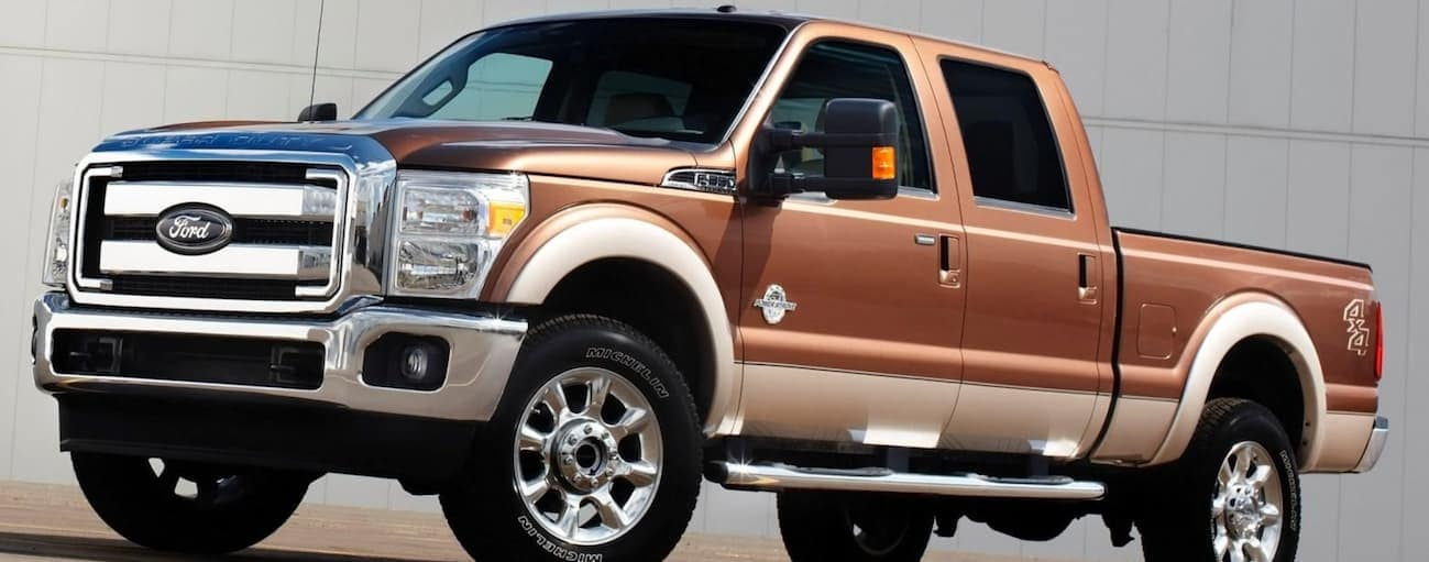 A brown 2016 Ford F-250 is parked in front of a white wall.